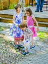 Little boy looking at a little girls easter eggs children having fun during family day celebration egg hunt activity outside in Stock Image