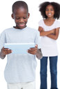 Little boy looking at a tablet pc with his sister on white background Royalty Free Stock Image