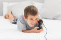 Little boy lying on bed playing video games at home Stock Images