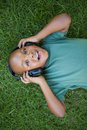 Little boy lying on grass listening to music smiling at camera a sunny day Stock Photo