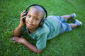 Little boy lying on grass listening to music smiling at camera a sunny day Stock Photos