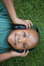 Little boy lying on grass listening to music smiling at camera a sunny day Stock Images