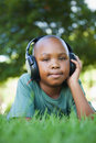 Little boy lying on grass listening to music smiling at camera a sunny day Royalty Free Stock Photography