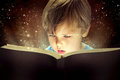 Little boy and the magic book Stock Photos