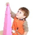 The little boy in montessori kindergarten collects pink pyramid isolated on white background Royalty Free Stock Photos