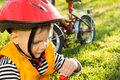 Little boy out cycling drinking bottled water sitting on green grass with his bike parked alongside and wearing a safety helmet Stock Photo
