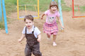 Little boy in overalls runs away from girl on warm sunny day Royalty Free Stock Image