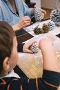 Little boy painting pine cones for christmas and his mother are Stock Image