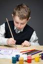 Little boy painting something portrait of with paints and pencils concept of arts and hobby Stock Images