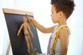 A little boy paints the wooden man near easel Royalty Free Stock Images