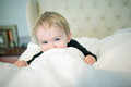 Little boy peeking over covers toddler on bed with white comforter the smiing with his eyes Stock Photos
