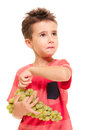 Little boy picks up berry bunch grapes isolated white Stock Photo