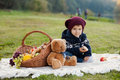 Little boy on a picnic with basket and teddy bear Stock Photo