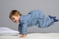 Little boy playful wearing blue pyjamas in bed Royalty Free Stock Image