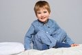 Little boy playful wearing blue pyjamas in bed Stock Photo