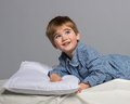 Little boy playful wearing blue pyjamas in bed Stock Image