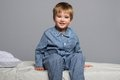 Little boy playful wearing blue pyjamas in bed Royalty Free Stock Photo