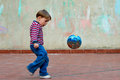Little boy playing with a ball in the back yard captured just before shooting the strong expression on his face Royalty Free Stock Photo