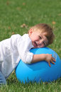 Little boy playing with blue ball cute blond outside a big Stock Photos