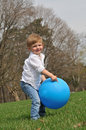 Little boy playing with blue ball cute blond outside a big Stock Photo
