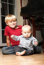 Little boy playing with a brother blond his newborn baby and fortepiano in the background indoor Stock Image