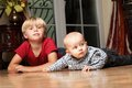 Little boy playing with a brother blond his newborn baby indoor Royalty Free Stock Images