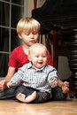 Little boy playing with a brother blond his newborn baby indoor Royalty Free Stock Photos