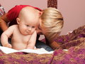 Little boy playing with a brother blond his newborn baby indoor Stock Photos