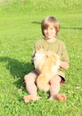 Little boy playing with a cat sitting barefoot orrange and white on meadow Stock Photo