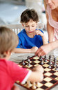 Little boy playing chess with his family Stock Images