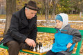 Little boy playing chess with his grandfather sitting back comfortably on a park bench waiting for to make Stock Photos