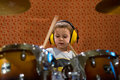 Little boy playing drums with protection headphones photo of ar rehearsal Royalty Free Stock Image