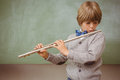 Little boy playing flute in classroom portrait of cute Royalty Free Stock Photo