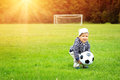 Little boy playing football on the field with gates Royalty Free Stock Photo