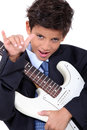 A little boy playing guitar and doing the horn sign Royalty Free Stock Image