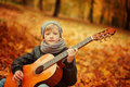 Little boy playing guitar on nature background, autumn day. Children's interest in music .