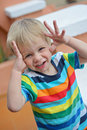 Little boy playing hide and seek in stripen t shirt face under hands Royalty Free Stock Photos