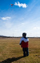 Little boy playing with a kite in a field Stock Photography