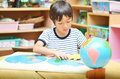 Little boy playing with puzzle of map in class Royalty Free Stock Photo