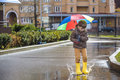 Little boy playing in rainy summer park. Child with colorful rainbow umbrella, waterproof coat and boots jumping in puddle and mud