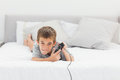 Little boy playing video games lying on bed at home Royalty Free Stock Image