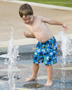 Little boy playing in a water fountain. Royalty Free Stock Photo