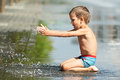 Little boy playing with water in a puddle Royalty Free Stock Photo