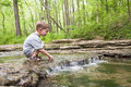 Little boy playing in waterfall young sitting a creek with a car a small Royalty Free Stock Images