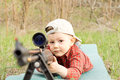Little boy playing wearing hat plays with shotgun outdoors Stock Photography
