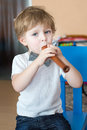 Little boy playing wooden flute indoor Royalty Free Stock Photo