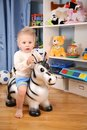 Little boy in playroom on zebra Royalty Free Stock Photos