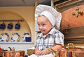 Little boy plays the cook sits on a kitchen table and Royalty Free Stock Image