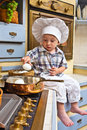 Little boy plays the cook sits on a kitchen table and Stock Photography