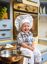 Little boy plays the cook sits on a kitchen table and Royalty Free Stock Photo